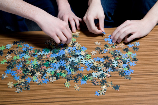 Men putting together puzzle, mid section